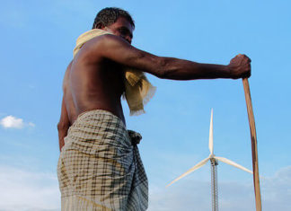 man standing in front of wind turbine